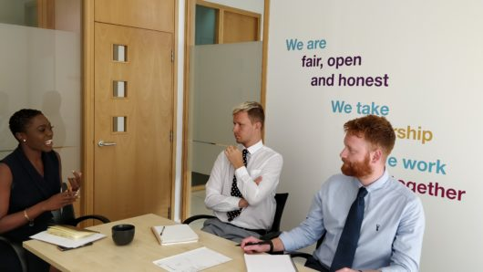 Bristol office - meeting room with people in and reed values on wall