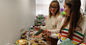 careers at reed - charity bake sale with consultants smiling