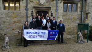 Reed Business School entrance - REED co-members holding banner with purpose of improving lives through work on it