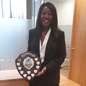 Helen Fontaine holding shield in Stratford Reed office